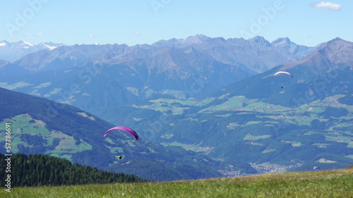 Paragliding over the mountains against clear blue sky,