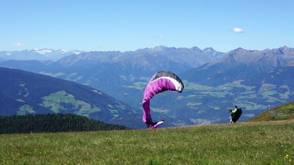Paraglider taking off from a mountain - start, Kronplatz, Italy