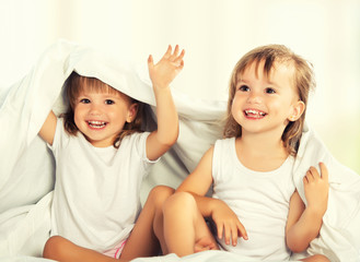 happy little girls twins sister in bed under the blanket having