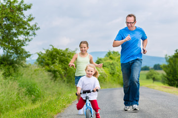 Vater und Töchter laufen auf Straße