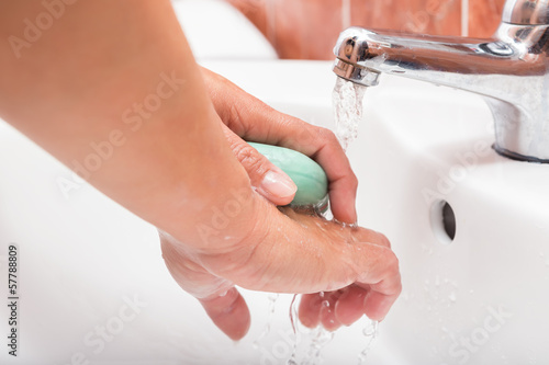 Washing hands with soap under the faucet