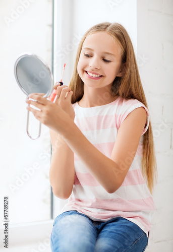teenage girl with lip gloss and mirror