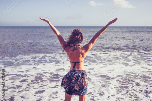 Young woman raising her arms at the beach
