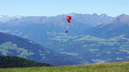 Paragliding over the mountains against clear blue sky, Italy