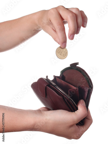 Hand puts a coin in the purse, isolated on white background