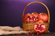 Ripe pomegranates on basket on wooden table on purple