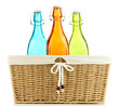 Color glass bottles in wicker basket, isolated on white