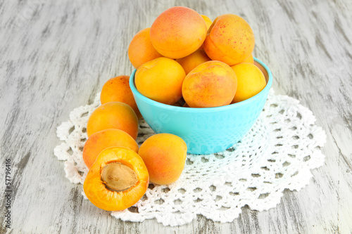 Fresh natural apricot in bowl on green wooden table