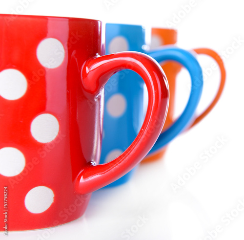Color polka dot mugs isolated on white