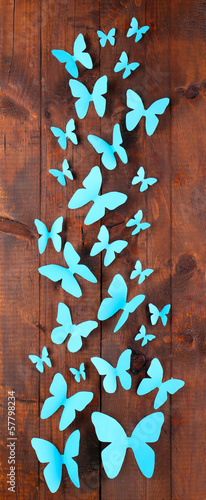 Paper blue butterflies on wooden board background