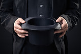 closeup of top hat in magician hands isolated on dark background