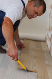 Man laying laminate flooring in a home.