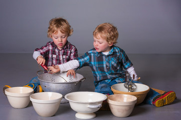 Cute blonde twins squabbling over cooking bowls and utensils