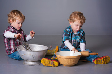 Cute blonde twins playing with cooking bowls and utensils