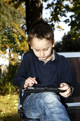 Kid with tablet outdoors in a park