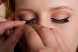 Professional makeup artist artist applies false eyelashes