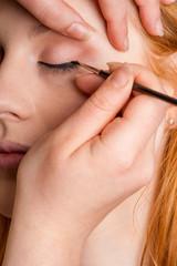 Professional makeup artist artist applies eyeliner