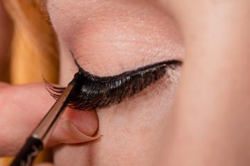 Professional makeup artist artist applies false eyelashes
