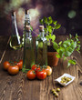 Bottles of olive oil, bunch of tomatoes, herbs, olives