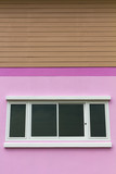 Pink walls with white opaque glass window under brown wood poster