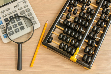 An old chinese abacus and modern calculator