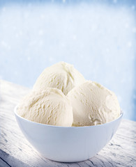 Vanilla ice-cream scoops in white cup.