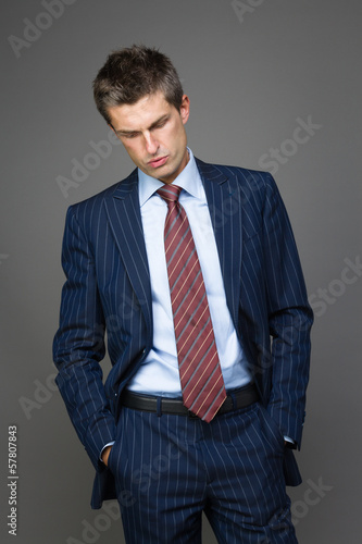 Elegant tired businessman looking down