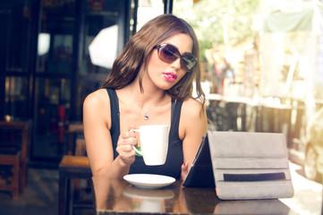Beautiful young woman having coffee outdoors