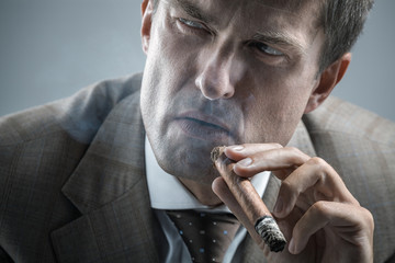 Elegant adult man smoking a cigar