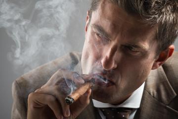hard gaze businessman while smoking a cuban cigar
