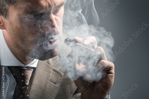 elegant adult man in a cloud of smoke