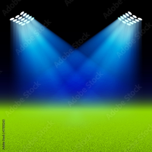 Bright spotlights illuminated green field stadium