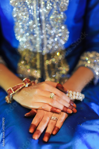 Bride's hand with diamond ring, wearing a blue wedding dress