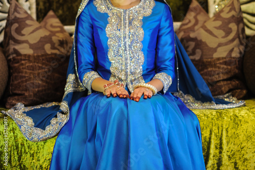 Bride Wearing a blue dress sitting on an altar, head not seen