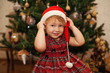 Smiling little girl in christmas hat sitting near the fir tree