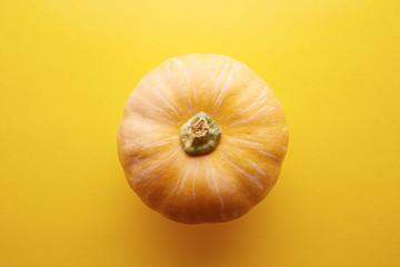 Whole raw pumpkin on yellow background