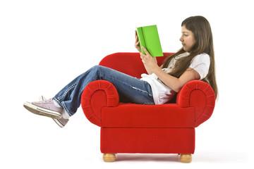 Mädchen ließt ein Buch im roten Sessel