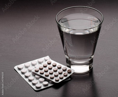 Water glass and medicaments on table