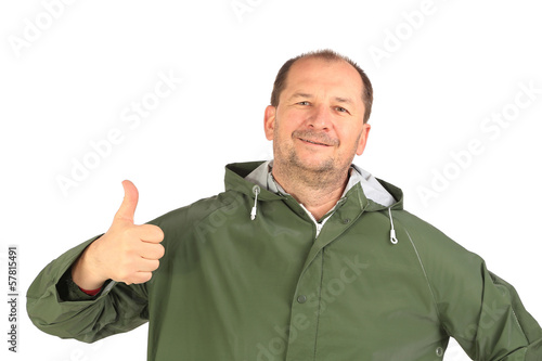 Man in coat shows thumb up.