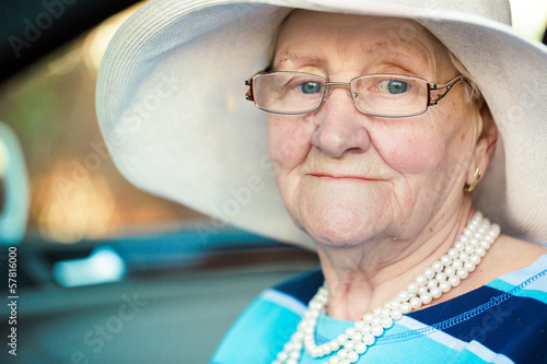 portrait of a mature woman in glasses and hat sitting in car