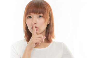 Asian woman making a keep  quiet gesture , isolated on white