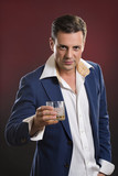 Stylish serious man in suit holding glass of alcohol