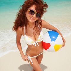 Fun woman with ball on the beach background