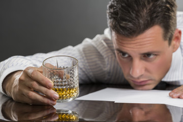 Sad businessman drinking alcohol at work