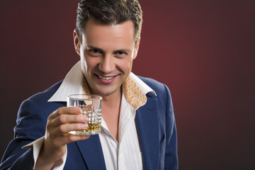 Cheerful businessman toasting with glass of alcohol