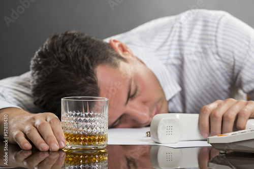 Sleeping man with drinking problems at work