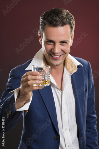 Smiling stylish man in suit cheering with a glass of alcohol