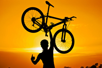 cyclist raising his bike with thumbs up silhouette