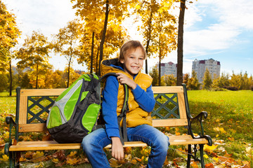 School boy sitting on bench in autumn park