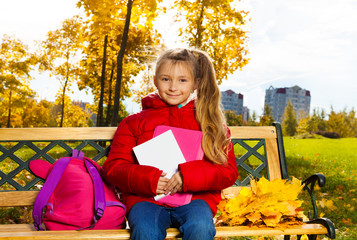 Cute 7 years old girl after school in autumn park